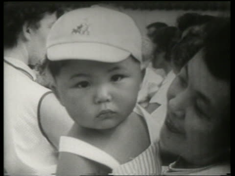 b/w close up of japanese woman holding baby / canadian national exhibition / sound - baseballmütze stock-videos und b-roll-filmmaterial