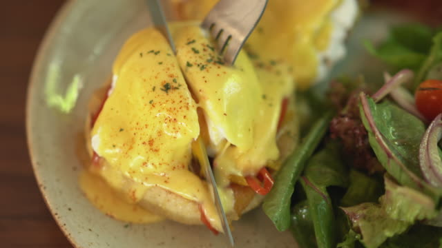 close up of knife and fork cutting poached egg and avocado sandwich - cooking pan video stock e b–roll