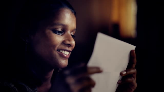 close up of late teen girl reading letter and smiling. - messaggio video stock e b–roll