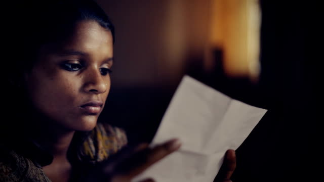 Close up of late teen girl reading letter.