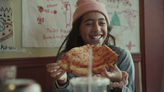 close up of laughing girl eating slice of cheese pizza / san francisco, california, united states - eating stock videos & royalty-free footage
