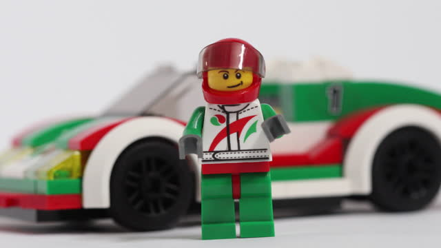 close up of lego figurine of speed race driver in front of racing car, studio arrangement, in danbury, essex, england, u.k., on friday, march 5, 2021. - extreme close up stock videos & royalty-free footage