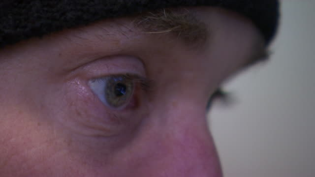 Close up of Lithuanian customs officer with reflection of computer monitor in their eyes