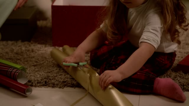 close up of little girl cutting wrapping paper for christmas presents - christmas wrapping paper stock videos & royalty-free footage