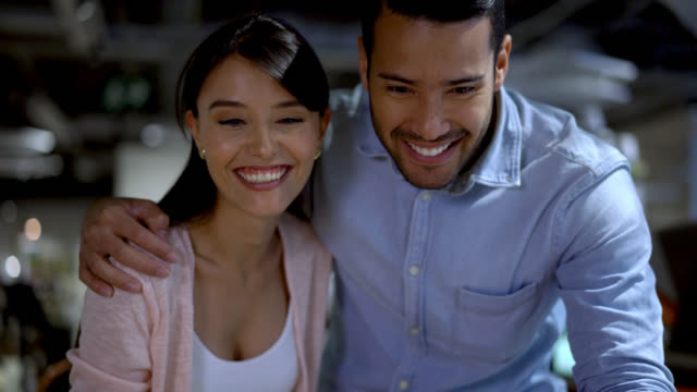 Close up of loving couple touching a wooden dining table at a furniture store talking and laughing