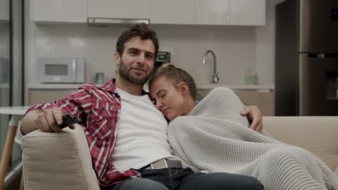 vidéos et rushes de fermez-vous vers le haut de l'homme aimant câlinant la belle femme à côté de lui sur le divan tout en regardant la tv - personnes féminines