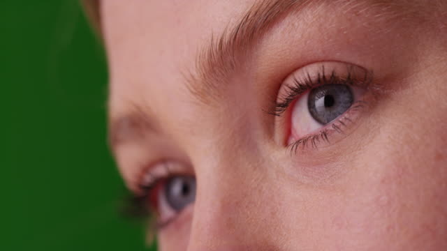 Close up of low angle view of Caucasian woman with blue eyes on green screen