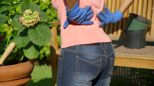 close up of lower back pain while gardening - backache stock videos & royalty-free footage