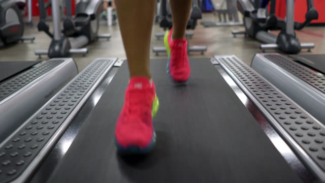 Close up of lower part of the body of unrecognizable woman running on a treadmill