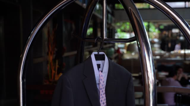 close up of luggage cart at hotel with a suit hanging on it - cart stock videos & royalty-free footage