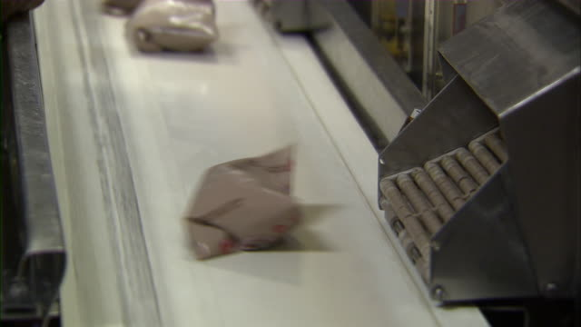 close up of machines loading plastic bags of chocolate milk onto a conveyor belt. - chocolate milk stock videos & royalty-free footage