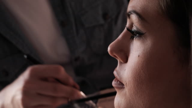 Close up of make-up artist applying contour and highlight foundation on woman's face.