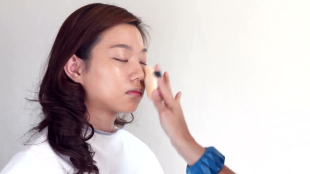 Close up of make-up artist applying foundation with a brush on young woman's face.