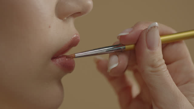 close up of make-up artist applying make-up - lip gloss with makeup brush to young model. - blusher stock videos & royalty-free footage