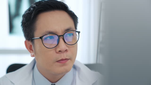 close up of male doctor wearing eye glasses and working on computer in medical room - clinic stock videos & royalty-free footage