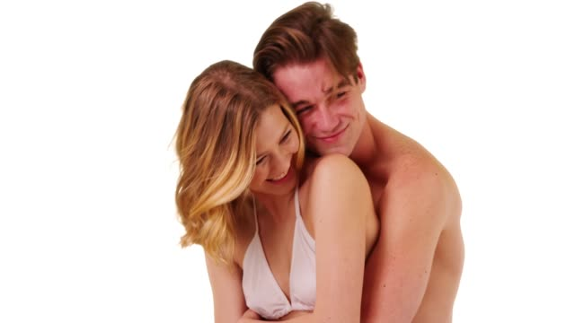 Close up of male in swim shorts hugging happy girlfriend from behind in studio