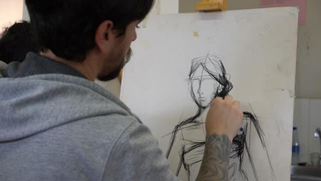 närbild på manlig student ritning på en duk med kol medan du tittar på kvinnlig modell - penna bildbanksvideor och videomaterial från bakom kulisserna
