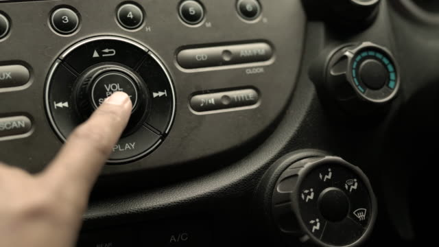 Close up of Male Turning Car Radio On