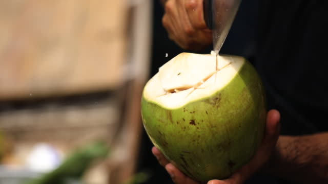 close up of man cutting a coconut with knife ,at the floating market in thailand. - bancarella video stock e b–roll