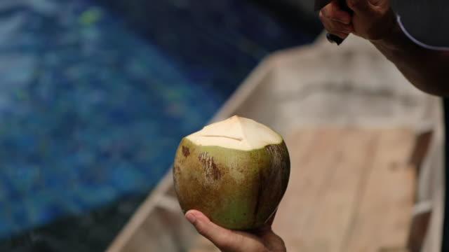 vídeos de stock, filmes e b-roll de feche acima do homem cortando um coco com faca, no mercado flutuante na tailândia. - vender