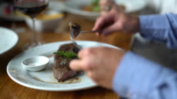Close up of man cutting a delicious steak and eating it