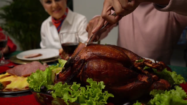close up of man cutting the turkey at a thanksgiving dinner with the family - thanksgiving stock videos & royalty-free footage
