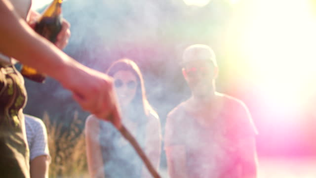 close up of man firing the grill with friends in background - grigliare video stock e b–roll