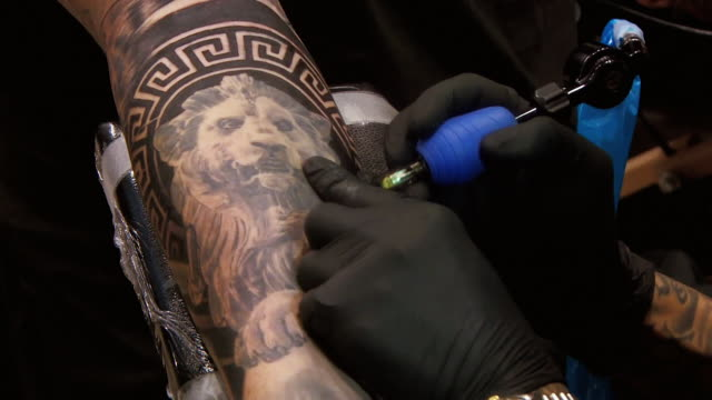 vidéos et rushes de close up of man getting his arm tattooed with a sleeve design, tattooist has tattoo covering neck, bristol - tatouage
