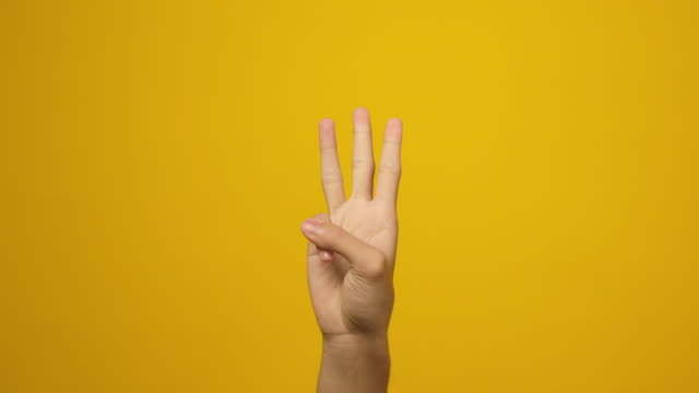 close up of man hand counting on his fingers up to 3, showing one, two, three hand sign while standing over yellow background in studio - human finger stock videos & royalty-free footage