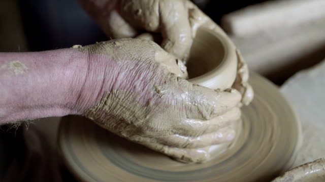 Close up of man hands working on clay mud