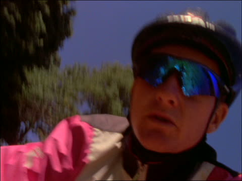 close up of man in helmet and sunglasses riding mountain bike