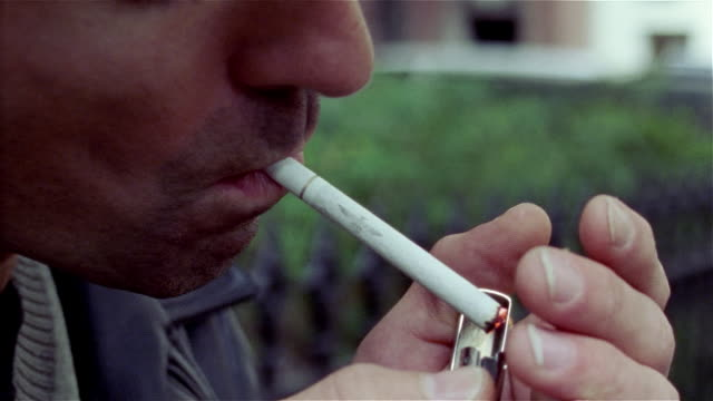 close up of man lighting cigarette with zippo lighter / smoking - smoking issues stock videos and b-roll footage