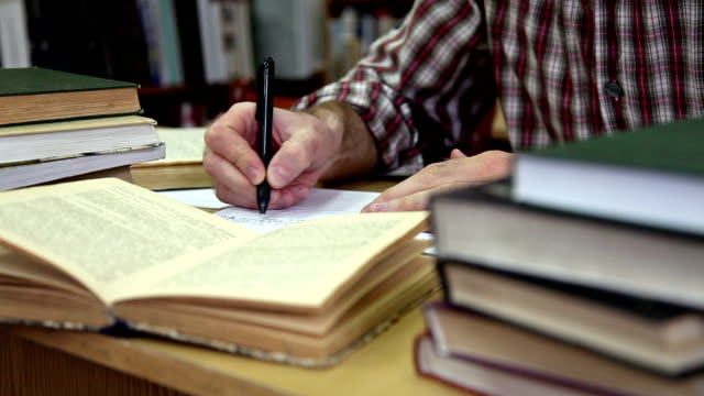 close up of man making notes in library - literature stock videos & royalty-free footage