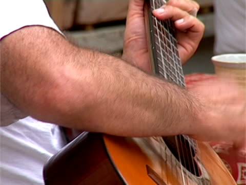 close up of man playing guitar - plucking an instrument stock videos and b-roll footage