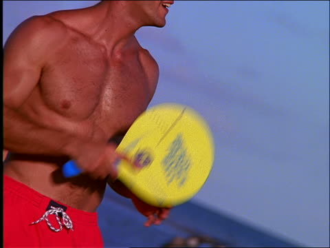 close up of man playing paddleball on beach / seagulls in background - one piece swimsuit stock videos & royalty-free footage
