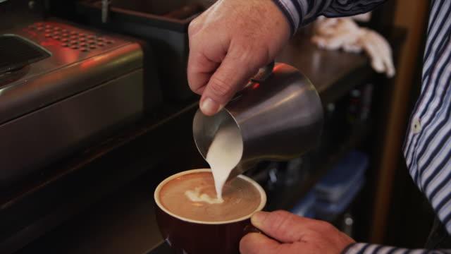 close up of man pouring milk into coffee / orem, utah, united states,  - orem utah stock videos & royalty-free footage