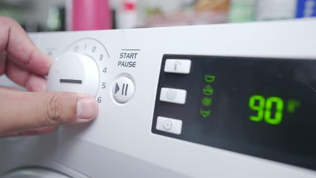 vídeos de stock, filmes e b-roll de close up of man putting laundry into washing machine - eficiência energética
