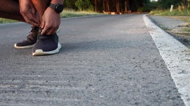 vídeos de stock e filmes b-roll de close up of man runner tying shoelaces on sport sneaker during running exercise in the morning sunrise - atleta