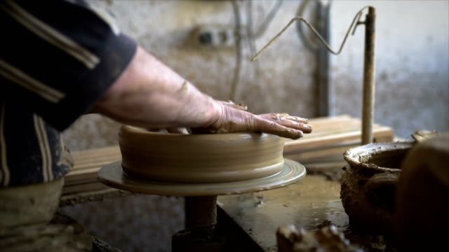 close up of man shaping clay into bowl on pottery wheel with sponge - potter's wheel stock videos & royalty-free footage