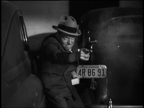 b/w close up of man shooting pistol near cars at night - handgun stock videos and b-roll footage