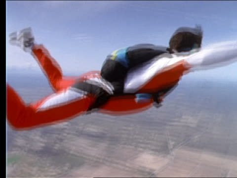 AERIAL close up of man skydiving / opens parachute