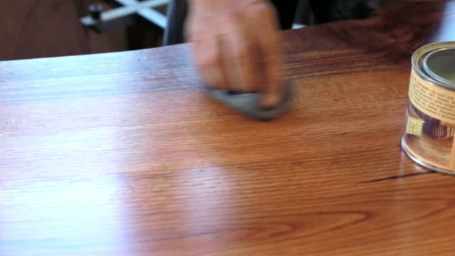 Close up of man staining wooden table