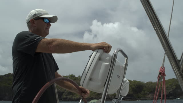 close up of man steering boat / st. vincent, st. vincent and the grenadines - one mature man only stock-videos und b-roll-filmmaterial