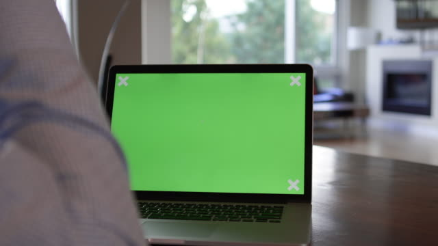 Close Up of Man Typing on Green Screen Laptop