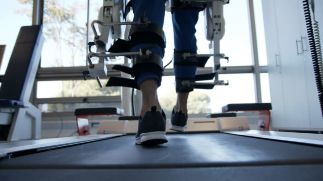 vídeos de stock e filmes b-roll de close up of man walking on treadmill with a help of a exoskeleton robot at a rehab clinic - recuperação