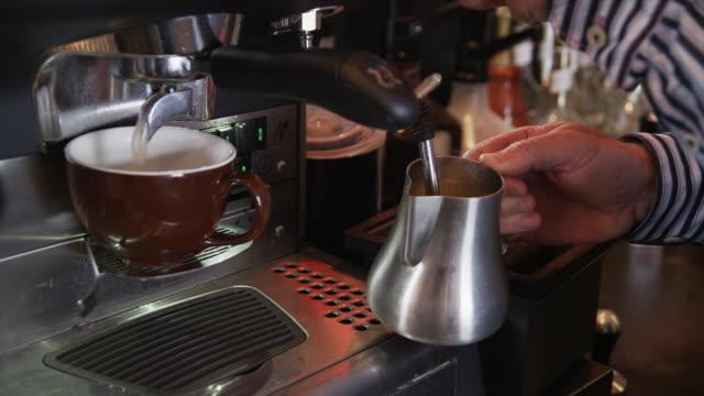 close up of man warming milk in coffee maker / orem, utah, united states,  - bricco video stock e b–roll