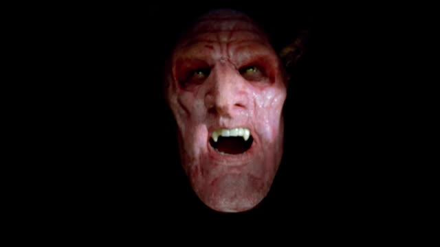 vídeos de stock, filmes e b-roll de close up of man wearing devil mask / looking at camera - evil