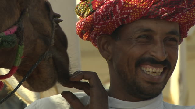 close up of man with camel pushkar rajasthan india - dhoti video stock e b–roll