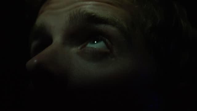 vídeos de stock e filmes b-roll de close up of mans face in a dark room with blinking lights - dark