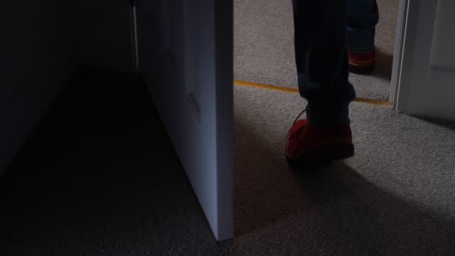 Close up of man's feet, leaving a dark room.